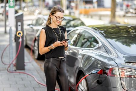 Femme, charge, électrique, voiture, dehors Banque d'images - 84948448