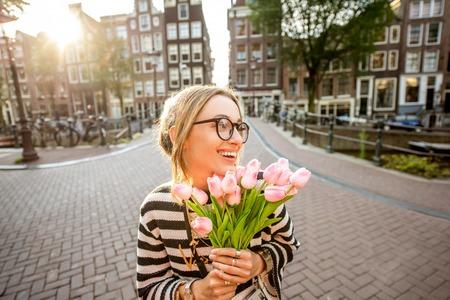 Vrouw met tulpen in de stad van Amsterdam