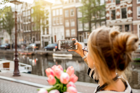 Vrouw die in de stad van Amsterdam fotografeert