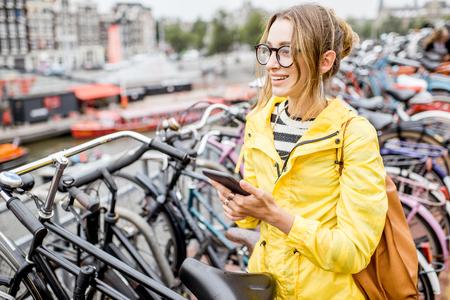 자전거 주차장에서 전화를 가진 여자 스톡 콘텐츠