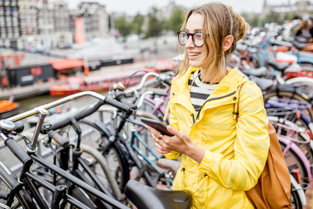 Woman with phone at the bicycle parking
