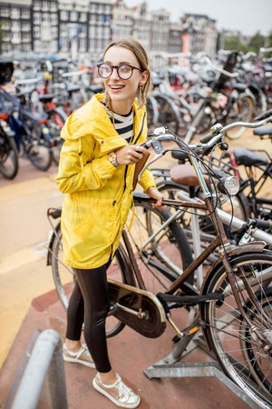 Woman parking a bicycle in Amsterdam Фото со стока