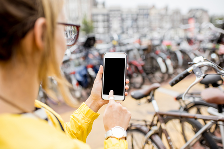 Holding a phone on the bicycle parking background Zdjęcie Seryjne