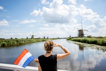 Woman near the old windmills in Netherlands Standard-Bild