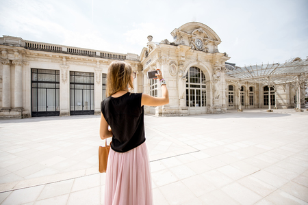 Woman near the old beautiful building in Vichy city, France