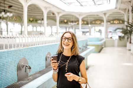 Woman in the old pump room with thermal water