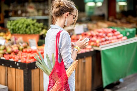 Woman with phone at the food market