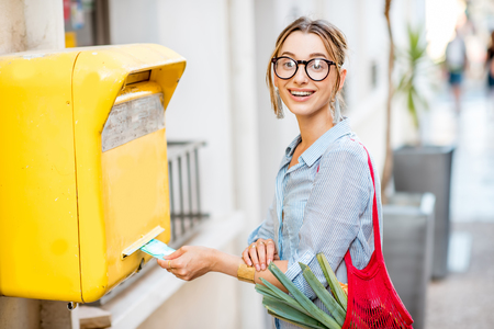 Woman using old mailbox outdoors