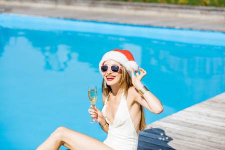 Woman in xmas hat at the swimming pool Stock Photo