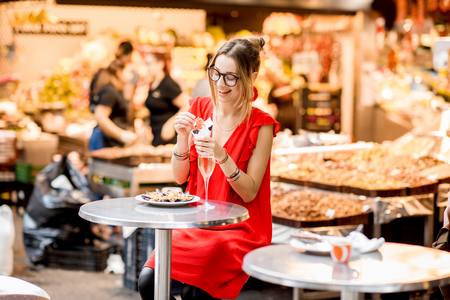 Young woman in red dress eating jamon traditional spanish dry-cured ham sitting at the Barcelona food market Stock Photo