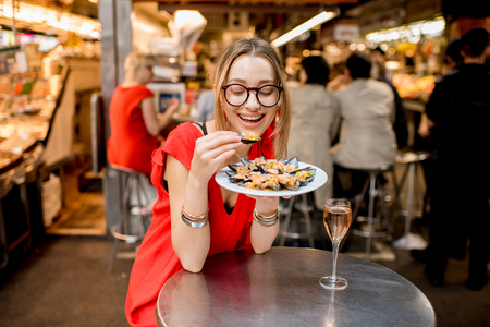 Young woman in red dress having lunch with mussels and rose wine sitting at the food market Stock Photo