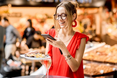 Young woman in red dress photographing plate of mussels with glass of wine sitting at the food market Stock Photo
