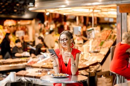 昼食を食品市場に座ってバラのワインとムール貝の赤いドレスの若い女性