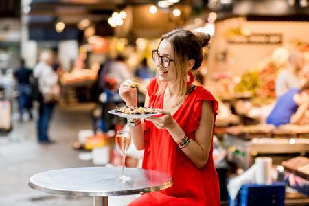Jonge vrouw in rode kleding die lunch met mosselen en roze wijnzitting hebben bij de voedselmarkt