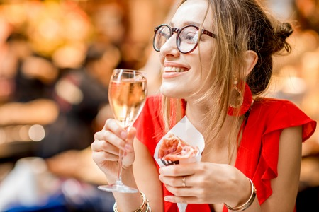 Young woman in red dress eating jamon traditional spanish dry-cured ham with glass of wine sitting at the Barcelona food market