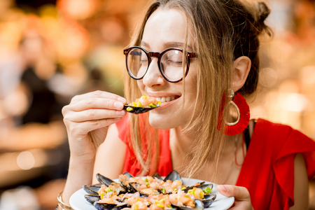 Portrait of a young woman in red dress having lunch with mussels and rose wine sitting at the food market