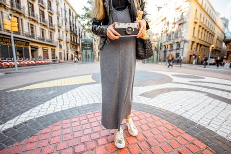 Young woman tourist standing with photo camera on the central street with famous colorful tiles in Barcelona city