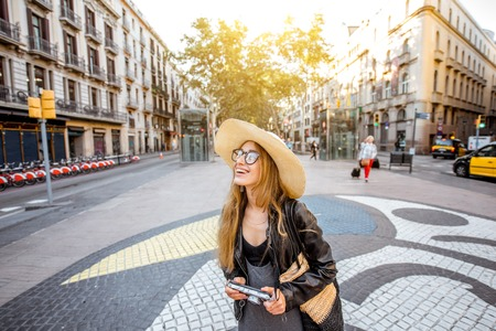 Young woman tourist standing on the central street with famous colorful tiles in Barcelona city