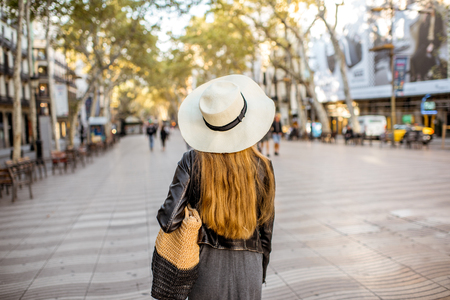 Young woman tourist in hat walking on the famous pedestrian boulevard in Barcelona city Stock Photo
