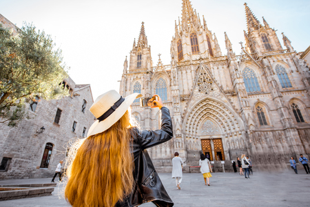 Young woman tourist photographing with phone famous saint Eulalia church during the morning light in Barcelona city