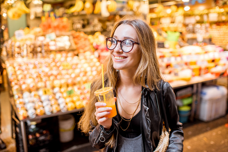 Young woman drinking orange juice in the famous food market in Barcelona city Stock Photo