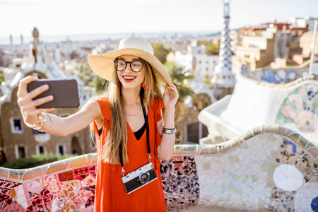 Portrait of a young woman tourist in red dress having fun visiting famous Guell park in Barcelona