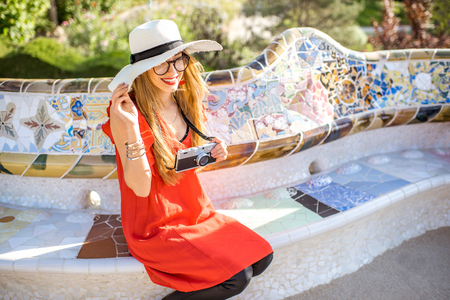 Young woman tourist in red dress sitting on the bench decorated with mosaic in the famous Guell park in Barcelona Stock Photo