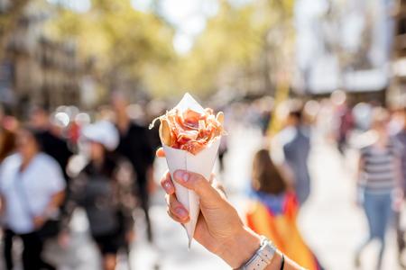 Tenendo il jamon tradizionale spagnolo a scatti di carne all'aperto sulla strada di Barcellona Archivio Fotografico - 89625003
