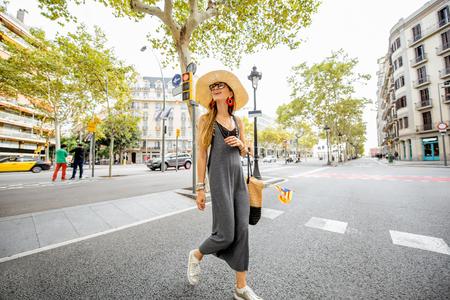 Young woman tourist walking with bag and catalan flag on the famous central boulevard in Barcelona city