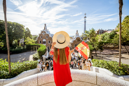 Woman tourist in red dress enjoying great view standing with spanish flag on the terrace in famous Guell park in Barcelona