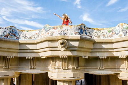 View on the beautiful terrace decorated with mosaic with happy woman tourist in Guell park in Barcelona Фото со стока