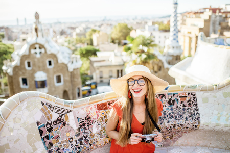 Portrait of a young woman tourist in red dress visiting famous Guell park in Barcelona