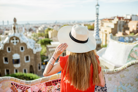 Young woman tourist in red dress enjoying great view on Barcelona city in famous Guell park Stock Photo