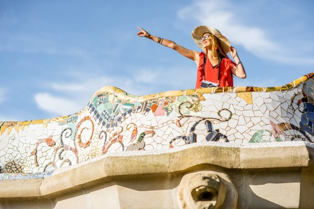 View on the beautiful terrace decorated with mosaic with happy woman tourist in Guell park in Barcelona Stock Photo