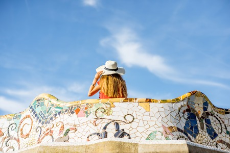 View on the beautiful terrace decorated with mosaic with happy woman tourist in Guell park in Barcelona Reklamní fotografie
