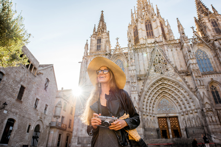 Young woman tourist standing in front of the famous saint Eulalia church during the morning light in Barcelona city