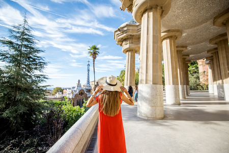 Happy woman tourist in red dress with hat standing back in famous Guell park in Barcelona Фото со стока