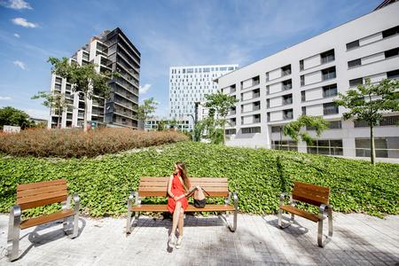 바르셀로나에서 현대 벤치에 앉아있는 여자와 함께 현대적인 사무실 안뜰에보기