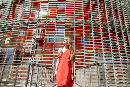 Lifestyle portrait of a woman in red dress in front of the modern building facade outdoors