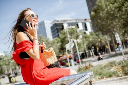 Lifestyle portrait of a business woman with phone in red dress sitting outdoors at the modern office district in Barcelona city