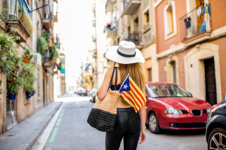Donna che cammina indietro con la bandiera catalana sulla vecchia strada vicino alla spiaggia di Barceloneta a Barcellona Archivio Fotografico - 88321590