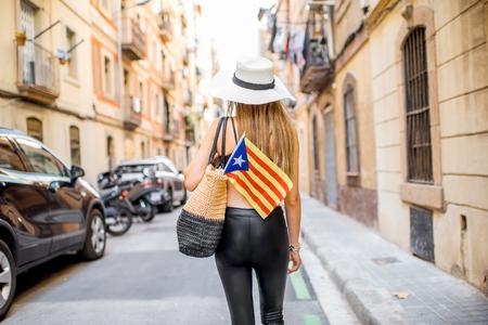 バルセロナ バルセロネータ ・ ビーチ近くの通りの古いに戻ってカタロニア語フラグと一緒に歩いている女性