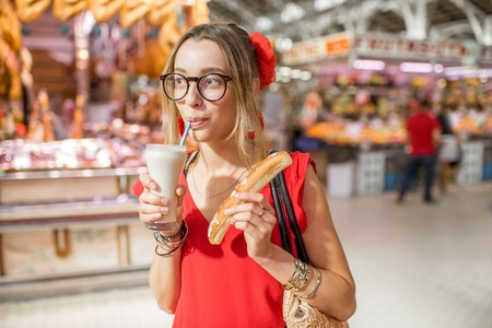 Woman portrait with Horchata, traditional spanish drink made from almonds, standing in the Central foodmarket of Valencia city Stock Photo