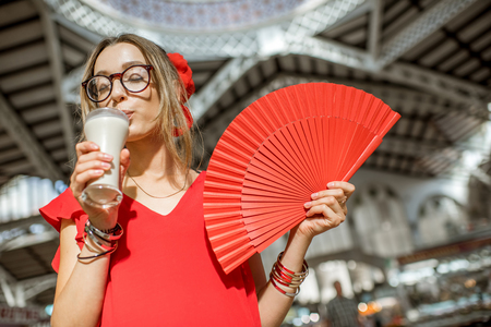 central european: Woman with Horchata, traditional spanish drink made from almonds, standing in the Central foodmarket of Valencia city