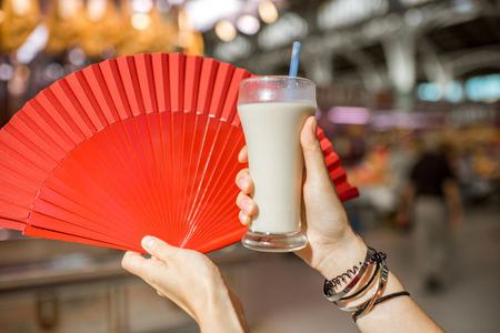 Holding Horchata, traditional spanish drink made from almonds, with red fan on the foodmarket background in Valencia city