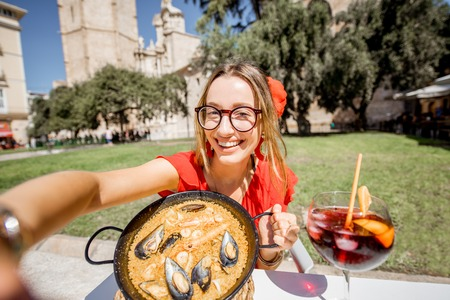 Young woman in red dress making selfie photo with sea Paella, traditional Valencian rice dish, sitting outdoors at the restaurant in the centre of the old town of Valencia