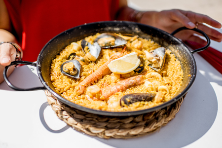 Pan with sea paella, Valencian rice dish, on the white table outdoors Stock Photo