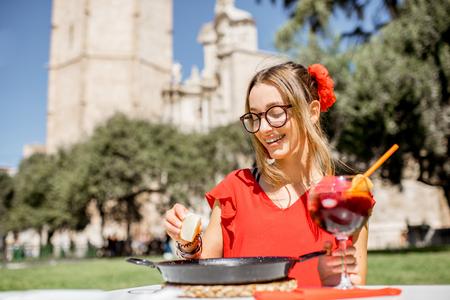 Junge Frau im roten Kleid mit Meer Paella, traditioneller Valencian-Reisteller, draußen sitzend im Restaurant in der Mitte der alten Stadt von Valencia Standard-Bild