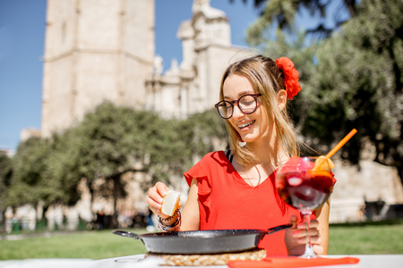 Young woman in red dress with sea Paella, traditional Valencian rice dish, sitting outdoors at the restaurant in the centre of the old town of Valencia