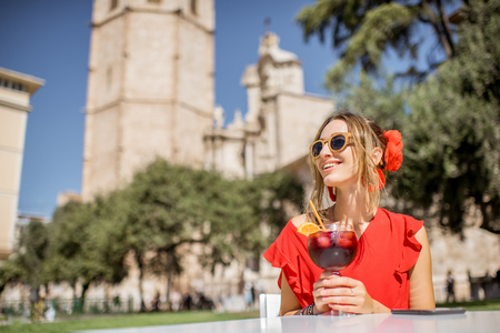 Young woman in red enjoying sangria, traditional spanish alcohol drink, sitting outdoors in the center of Valencia old town